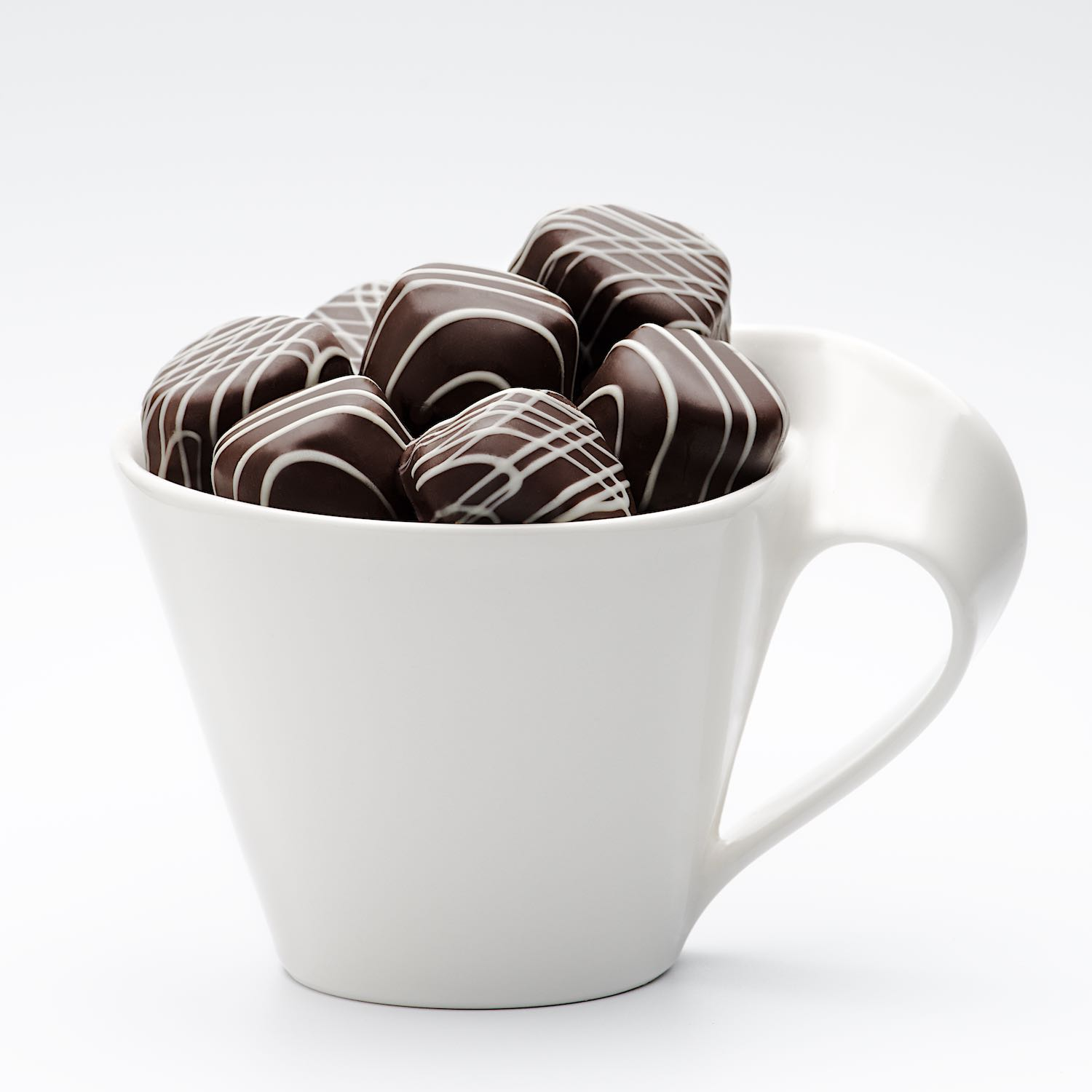 Dark chocolate candy in white coffee cup on white background © Bret Doss Commercial Food & Product Photography  Seattle