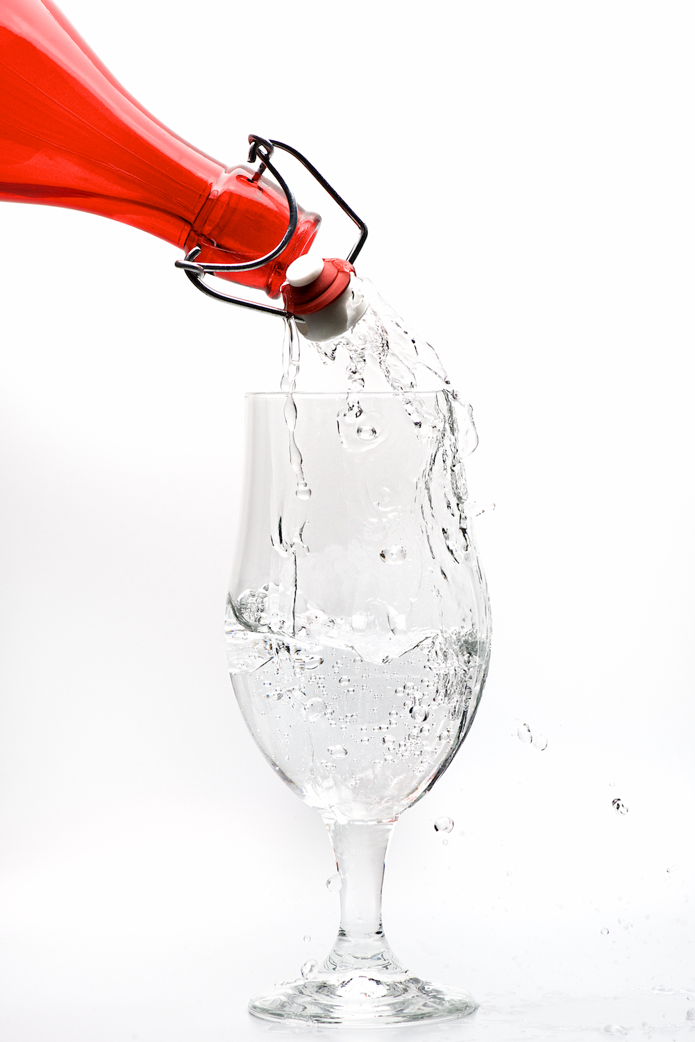Water pour splash from red bottle into stem glass on white background by Bret Doss Commercial Food & Product Photography  Seattle