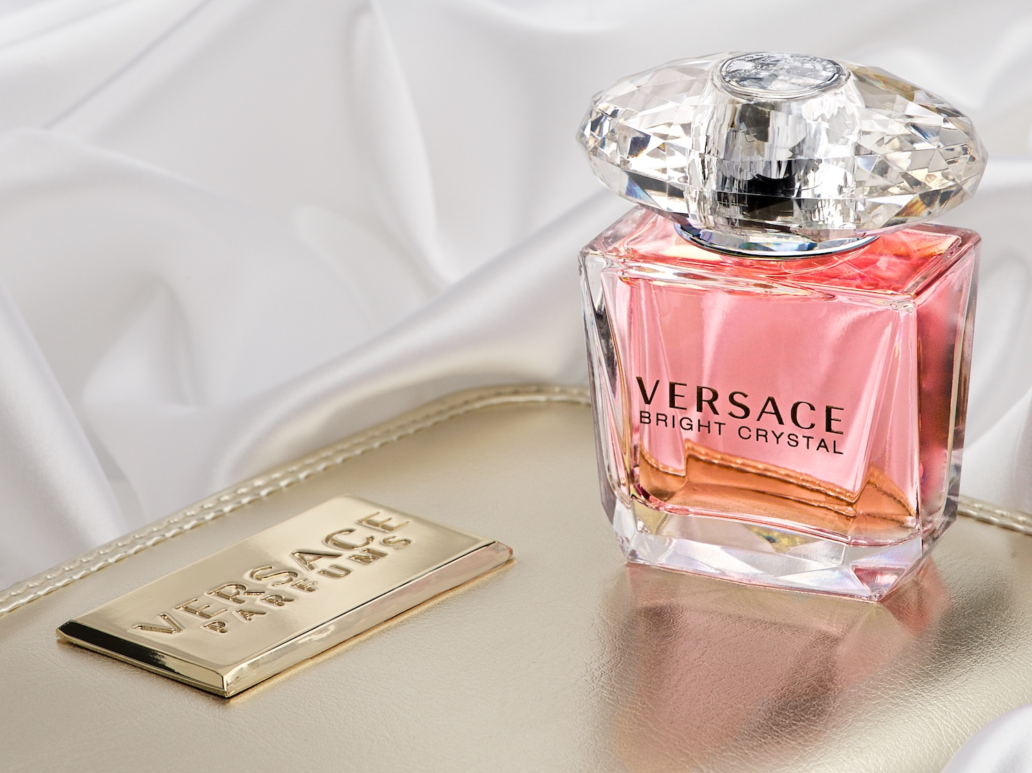 Versace Bright Crystal perfume bottle on gold case and satin by Bret Doss Commercial Product Photography Seattle
