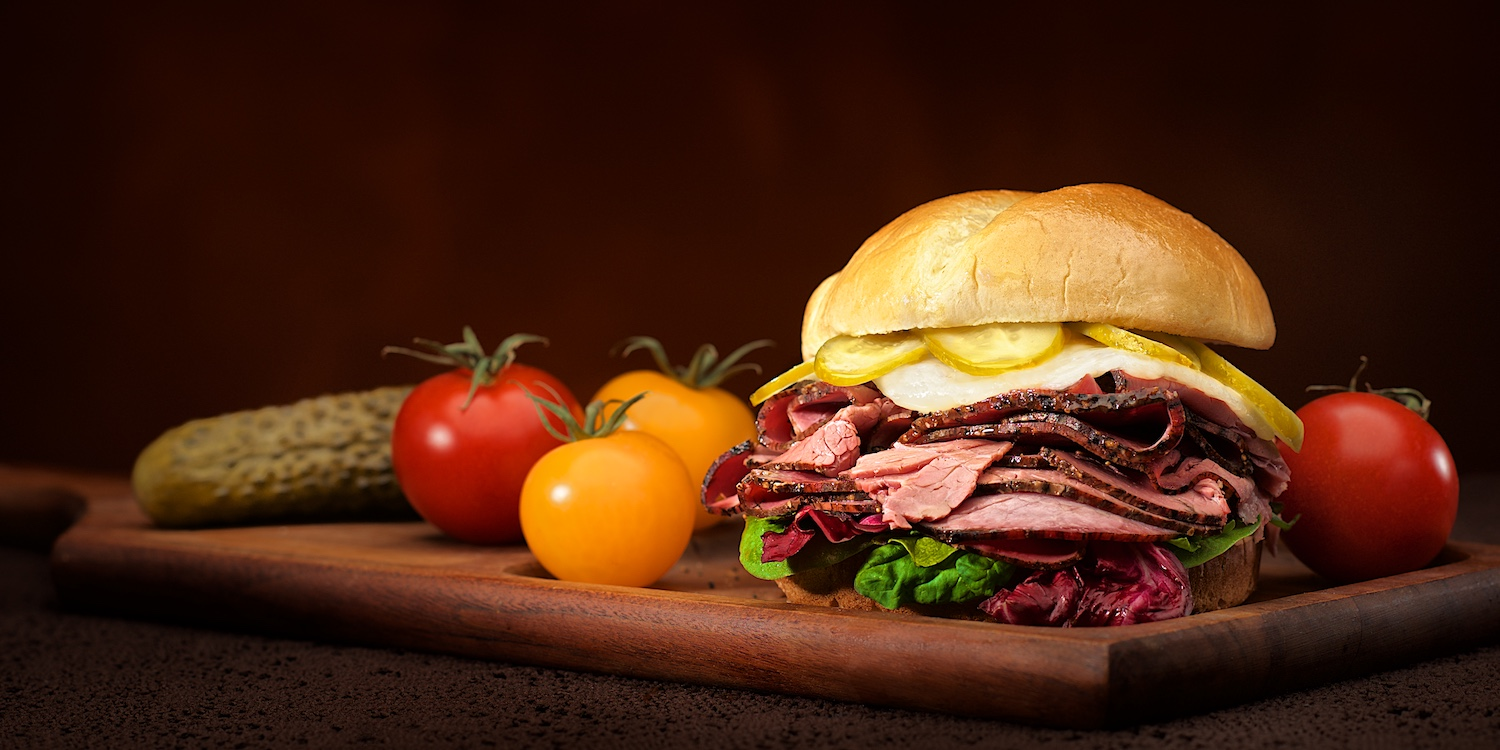 Pastrami & swiss cheese sandwich kaiser roll with pickles tomato lettuce mustard in warm light dark background by Bret Doss Commercial Food & Product Photography  Seattle